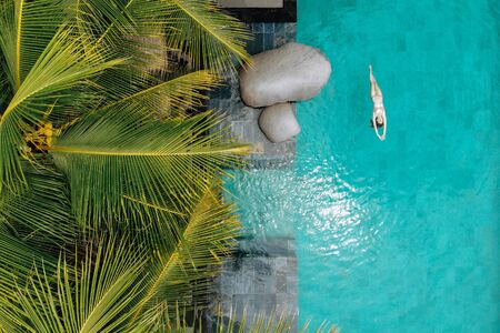 Aerial view of slim young woman in bikini swimming in luxury pool and palm trees.Vacation concept. Drone photo. 版權商用圖片