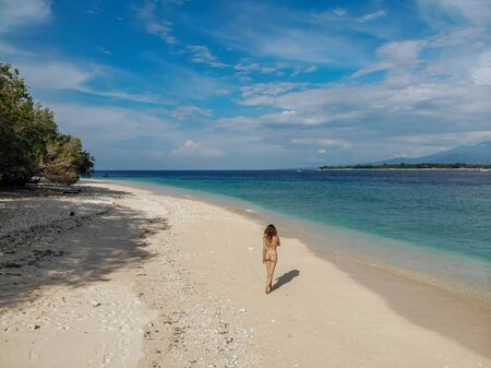 Back view of Woman in beige bikini walking on beach with turquoise ocean, blue sky. Gili Meno island, Bali, Indonesia. Tropical background and travel concept. Drone Photo. Imagens
