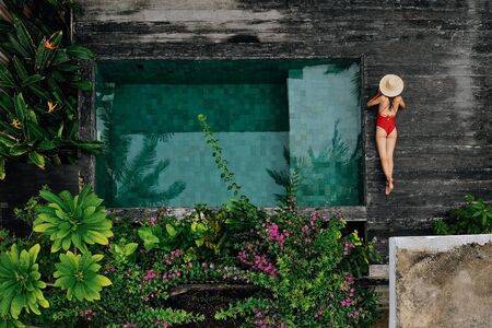Enjoying suntan. Vacation concept. Top view of slim young unrecognizable woman in red bikini and straw hat lying near swimming pool in jungle. Back view, without face.