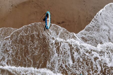 Aerial drone view of a woman on a surfboard on ocean beach of Bali Indonesia. Tropical background and travel sport concept