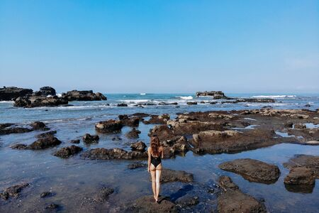 Aerial drone view of unrecognizable woman in black swimsuit enjoying beach with many stones and rocks in ocean. Bali Island, Indonesia.