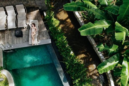 Aerial view of slim young woman in beige bikini relaxing and sunbathe near luxury swimming pool in green tropic in Ubud.Vacation concept. Drone photo. 版權商用圖片