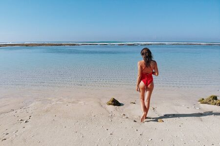 unrecognizable woman with sexy butt in red bikini standing on white sand tropical beach with blue clear water and jungle. Bali Indonesia. Tropical background and travel concept. Imagens