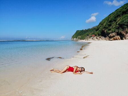 Sexy woman in red bikini relaxing on white sand tropical beach with blue clear water and jungle. Bali Indonesia. Tropical background and travel concept.