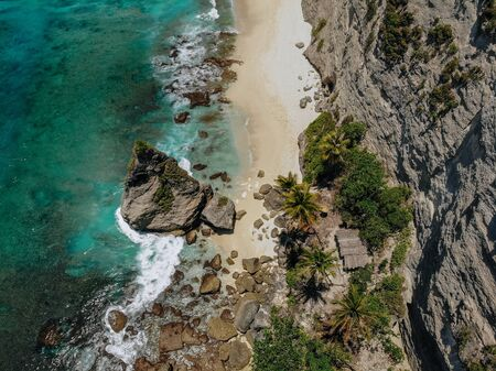 Aerial drone photo of tropical beach, sea rocks, turquoise ocean and palm trees. Atuh beach, Nusa Penida island, Bali, Indonesia. Tropical background and travel concept.