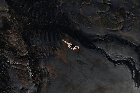 Aerial drone view of woman in black swimsuit lying relaxing on black sand beach. Bali Island, Indonesia. Imagens