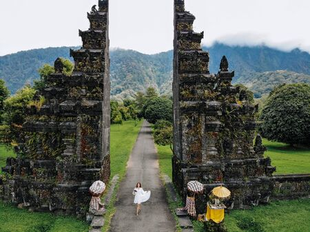 Tourist woman take a photo of yourself with drone near Traditional Balinese Hindu gate Candi Bentar close to Bedugul, Indonesia. Vacation on Bali.