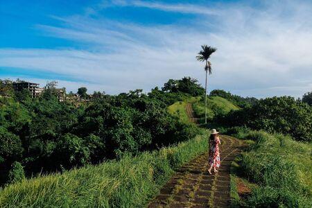 Young beautiful woman walking on Campuhan Ridge way of artists, in Bali, Ubud. Beautiful calm sunny morning. Imagens