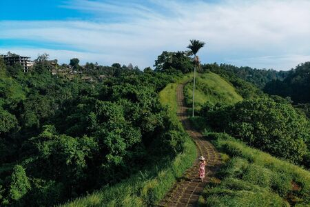 Young traveller woman in red dress and straw hat walking on Campuhan Ridge way of artists, in Bali, Ubud. Drone photo.