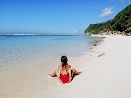 Back view of Sexy woman in red bikini sitting and posing on white sand tropical beach with blue clear water and jungle. Bali Indonesia. Tropical background and travel concept. Imagens