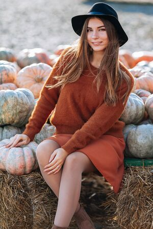Portrait of happy woman sitting on straw on farmers market with orange pumpkin in brown sweater and hat. Cozy autumn vibes Halloween, Thanksgiving day 版權商用圖片