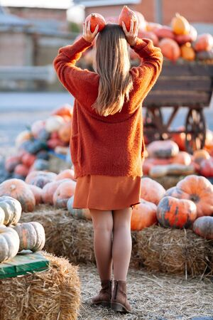 Back view of woman with small pumpkin in hand above head near wooden wagon with pumpkin on farmers market in brown sweater. Cozy autumn vibes Halloween, Thanksgiving day