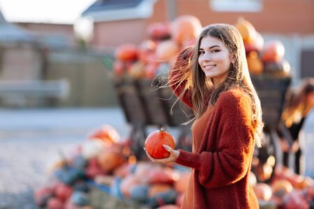 Portrait of happy smile woman with small pumpkin in hand near wooden wagon with pumpkin on farmers market in brown sweater, dress and hat. Cozy autumn vibes Halloween, Thanksgiving day