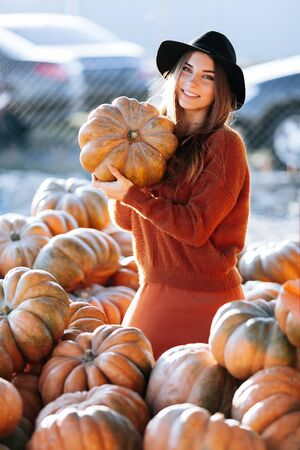 Portrait of happy woman with ripe orange pumpkin in hands on background of farmers market in brown sweater and hat. Cozy autumn vibes Halloween, Thanksgiving day. 版權商用圖片