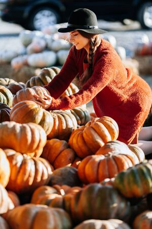 Portrait of happy woman choosing ripe orange pumpkin on farmers market in brown sweater, dress. Cozy autumn vibes Halloween, Thanksgiving day 版權商用圖片