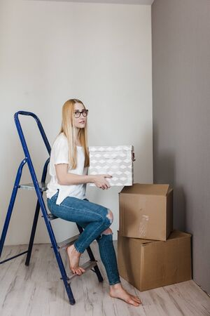 Young woman moving in her new house and doing a home makeover, she is sitting on the ladder with many cardboard boxes around