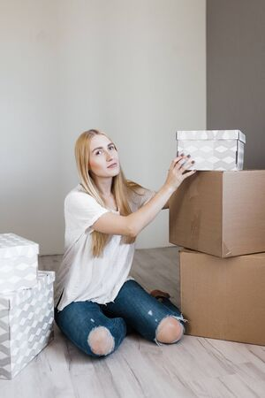 young blonde smile woman surrounded cardboard boxes sitting on floor after relocation