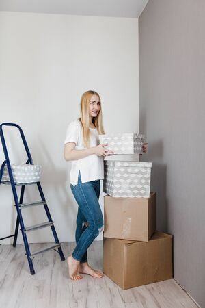 Young woman moving in her new house and doing a home makeover, she is standing near many cardboard boxes around