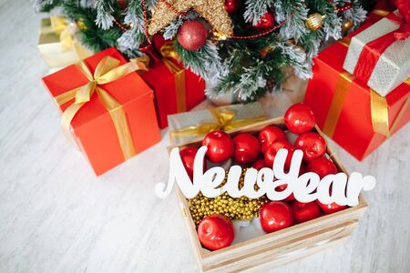 Christmas Gifts wrapped in classic red paper and wooden letters New Year, background with xmas tree. Copy space