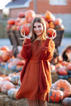 Portrait of happy smile woman with ripe orange pumpkins in hands near wagon with orange pumpkin on farmers market in brown sweater, dress. Cozy autumn vibes Halloween, Thanksgiving day.