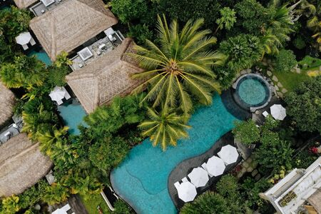 Aerial view of luxury hotel with straw roof villas and swimming pools in tropical jungle and palm trees. Luxurious villa, pavilion in forest, Ubud, Bali