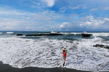Aerial view of back view woman in red bikini and straw hat enjoing ocean with rocks and beach with black sand . Vacation in Bali. Photo from drone.