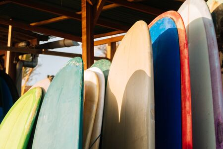 Set of colorful surfboard for rent on the beach. Multicolored surf boards different sizes and colors surfing boards on stand, surfboards rental place Banco de Imagens - 132110936