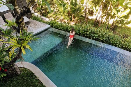 Back view of woman in red bikini relaxing in infinity pool in Bali admires a beautiful view of the palm trees.Luxury holiday.Girl resting on the island of Bali. Copy space. Vacation concept Stock Photo - 133800535