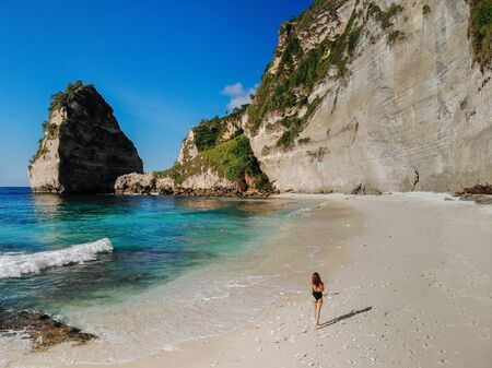 Back view of Woman in bikini walking on beach with sea rocks and turquoise ocean, blue sky. Atuh beach, Nusa Penida island, Bali, Indonesia. Tropical background and travel concept. Drone Photo