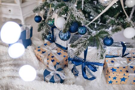 Christmas Gifts wrapped in silver and blue paper, background with xmas lights bokeh of blurred under Christmas tree.