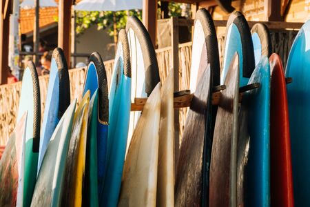 Set of colorful surfboard for rent on the beach. Multicolored surf boards different sizes and colors surfing boards on stand, surfboards rental place