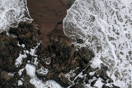 Top view aerial photo from flying drone of ocean landscape with big waves and rocks on black sand beach. Copy space for your advertising text message or promotional content.Perfect website background