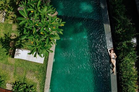 Top view of woman in beige bikini relaxing on edgeof infinity pool around palm trees and jungle. Luxury holiday.Girl resting on the island of Bali. Copy space. Vacation concept