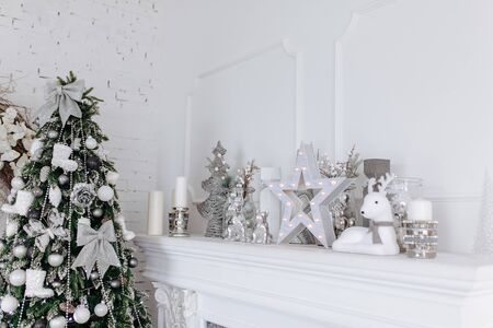 Christmas and New Year white and silver decorations on fireplace in white interior room with New year tree. Xmas concept