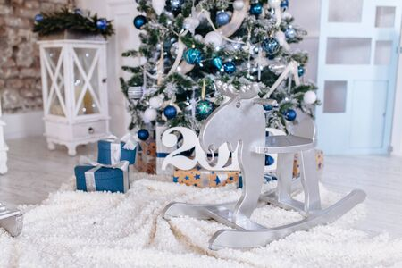 Christmas and New Year toy wooden deer in decorated interior room with presents and New year tree close up. Copy space