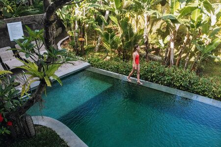 Woman in a private pool in Bali admires a beautiful view of the palm trees.Luxury holiday.Woman resting in the pool with a beautiful view of the palm trees on the island of Bali.Fruit in the pool. 版權商用圖片