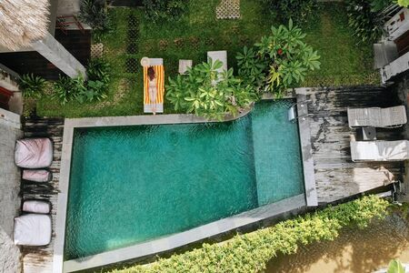Top view of unrecognizable slim young woman in beige bikini relaxing and sunbathe near luxury swimming pool in green tropic in Ubud.Vacation concept. Drone photo.