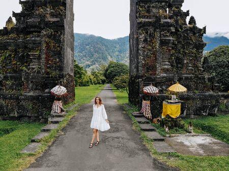 Tourist woman posing near Traditional Balinese Hindu gate Candi Bentar close to Bedugul, Bratan lake Bali island Indonesia. Vacation on Bali Drone photo. 版權商用圖片