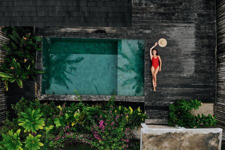 Aerial drone photo of happy Woman in red swimsuit relaxing near private pool with flowers and greenery around, Bali. Tropical background and travel concept 版權商用圖片