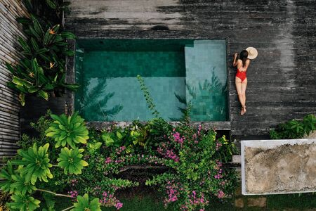 Aerial drone photo of unrecognizable Woman in red swimsuit relaxing near private pool with flowers and greenery around, Bali. Tropical background and travel concept