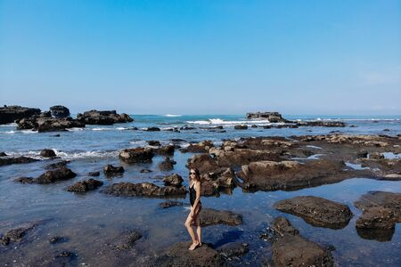 Aerial drone view of unrecognizable woman in black swimsuit enjoying beach with many stones and rocks in ocean. Bali Island, Indonesia. 版權商用圖片 - 138990375