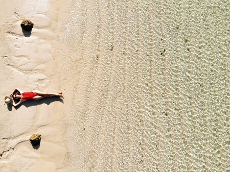 Aerial view of young woman in red bikini lying on beach with white sand, turquoise water of the Indian Ocean. Bali Island, Indonesia. Photo from drone. Tropical background and travel concept.