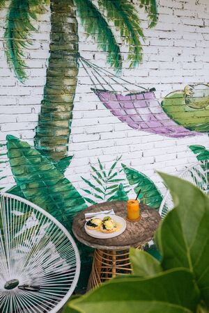 Healthy Breakfast with Bread Toast and Poached Egg with spinach, avocado and Orange smoothie on wooden table.Modern design graffiti on a brick wall with avocado in a hammock. 版權商用圖片