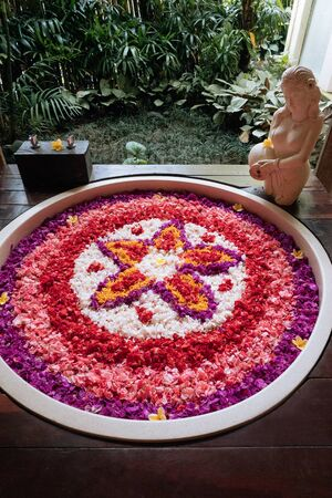 Stone round bath tub with flower shaped petals in pink,red,white colors near window with jungle view. Organic spa relaxation in luxury Bali bathroom. 版權商用圖片
