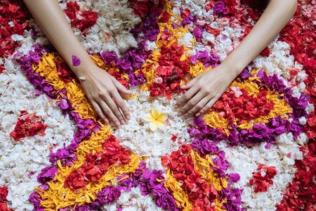 Top view womans hand on flowers petals in bathtub in luxury bathroom in hotel. Spa, self care, organic and skin care, beauty treatment concept. 版權商用圖片