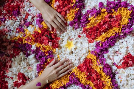 Top view womans hands touching flowers petals in bathtub in luxury bathroom in hotel. Spa, self care, organic and skin care, beauty treatment concept.