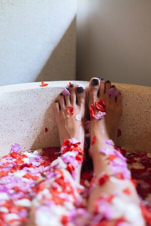 Beautiful female feet in outdoor bath with tropical flowers.Spa,organic and skin care concept. Woman legs in petals.