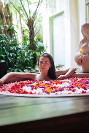 Close up portrait of Woman relaxing in round big bath with tropical flowers. Amazing huge bath tub in tropical jungle.Organic skin care in hot bath in luxury spa resort 版權商用圖片