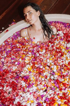 Beautiful young woman enjoying in outdoor spa. Luxury round bath tub. Natural organic tropical petals in the water: white, pink, red, violet. Beauty treatment concept