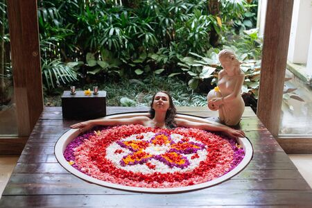 Beautiful young woman enjoying in outdoor spa. Luxury round bath tub with jungle view. Natural organic tropical petals in the water: white, pink, red, violet. Beauty treatment concept 版權商用圖片